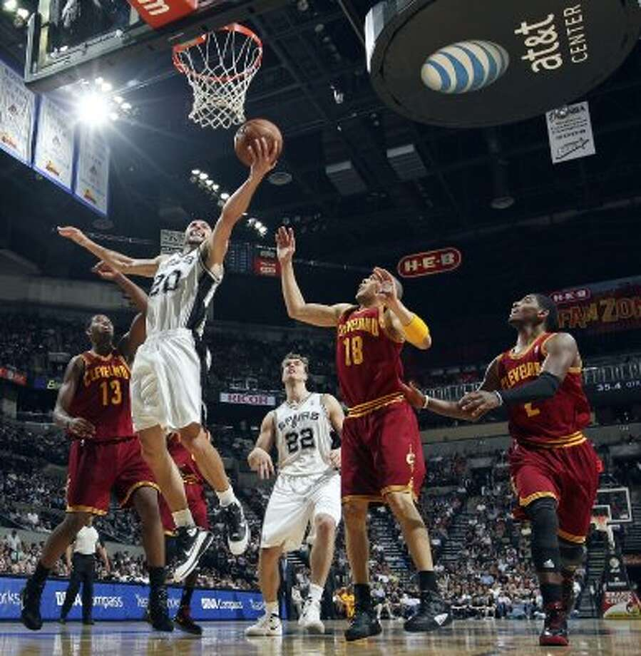 FOR SPORTS - San Antonio Spurs' Manu Ginobili shoots between Cleveland Cavaliers' Tristan Thompson (from left), Anthony Parker, and Kyrie Irving as teammate Tiago Splitter looks on during first half action Sunday April 22, 2012 at the AT&T Center. (PHOTO BY EDWARD A. ORNELAS/SAN ANTONIO EXPRESS-NEWS) (SAN ANTONIO EXPRESS-NEWS)
