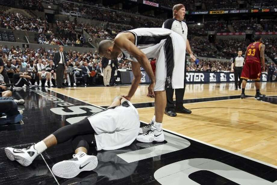 FOR SPORTS - San Antonio Spurs' Tony Parker (top) checks on teammate Danny Green after he was poked in the eye by Cleveland Cavaliers' Manny Harris during first half action Sunday April 22, 2012 at the AT&T Center. (PHOTO BY EDWARD A. ORNELAS/SAN ANTONIO EXPRESS-NEWS) (SAN ANTONIO EXPRESS-NEWS)