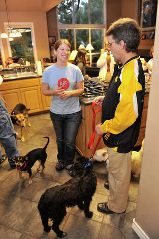 Virginia Davidson of Alamo Rescue Friends (ARF) talks to dog foster parent Dean Neuzil prior to loading the dogs for the journey to Nashua, New Hampshire. Photo: Robin Jerstad, Robin Jerstad/For The Express-News