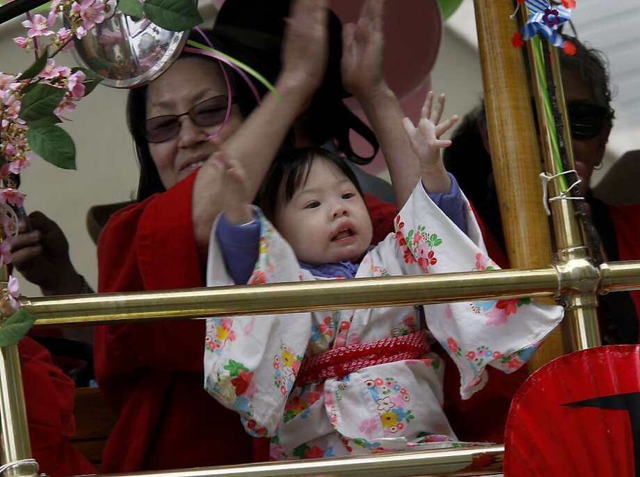 Little Cindy Nakamoto clapped in appreciation of the parade as she sat on her grandmother's lap. The Cherry Blossom Festival and parade celebrated its 45th year as one of California's most prominent celebrations of Asian traditions Sunday April 22, 2012. Photo: Brant Ward, The Chronicle