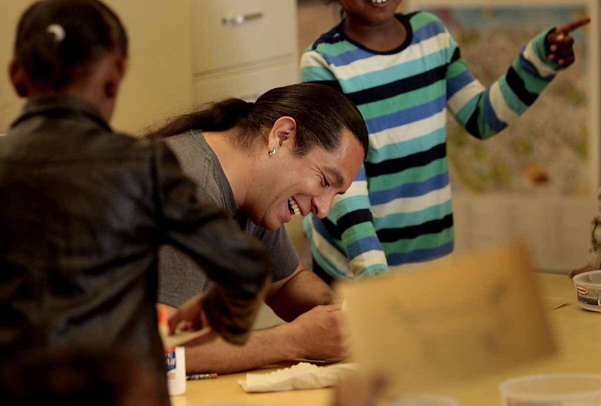 Eddie Madril laughs as he applies glue to the students Native American sand paintings. Eddie Madril is an artist in residence that teaches Native American culture and dance at Tenderloin Community School.
