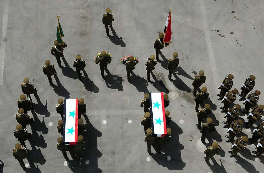 """A handout picture released by the Syrian Arab News Agency (SANA) shows Syrian security forces carrying the coffins of  comrades, who the ageancy said were killed in recent violence in the country, during a funeral procession outside the Tishrin military hospital in Damascus on April 22, 2012.  AFP PHOTO/HO  -- RESTRICTED TO EDITORIAL USE - MANDATORY CREDIT """"AFP PHOTO / HO / SANA"""" - NO MARKETING NO ADVERTISING CAMPAIGNS - DISTRIBUTED AS A SERVICE TO CLIENTS (Photo credit should read -/AFP/Getty Images) Photo: -, AFP/Getty Images"""