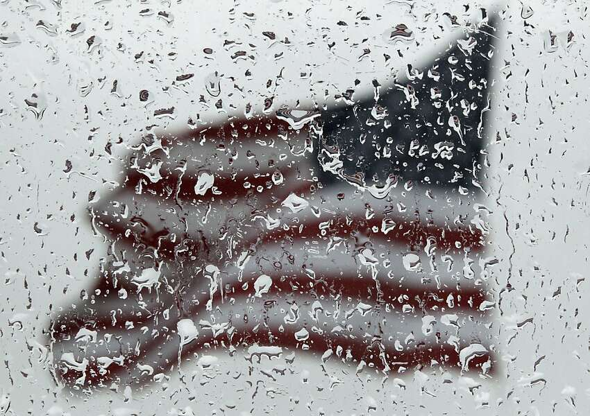 An American flag is seen through rain drops on a window as rain falls in Baltimore, Sunday, April 22, 2012. (AP Photo/Patrick Semansky)