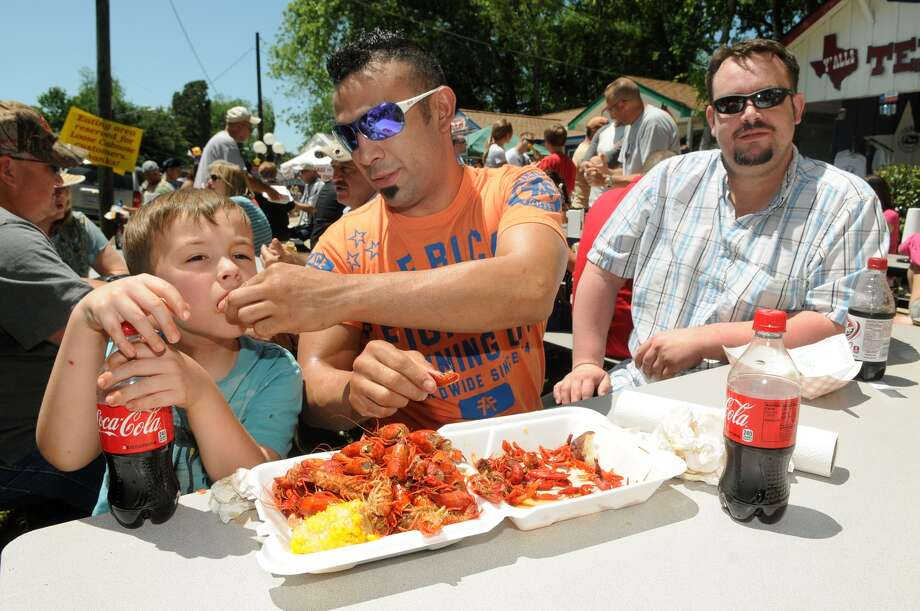 Rocky Rico, center, of Cypress, helps his son, Rocco, 7, with a crawfish from The Loose Caboose on Sunday, April 22, at the 26th annual Texas Crawfish & Music Festival in Old Town Spring. At right is Rico's friend, Hans Gerasimovski, of Detroit. Jerry Baker photo Photo: Jerry Baker, For The Chronicle