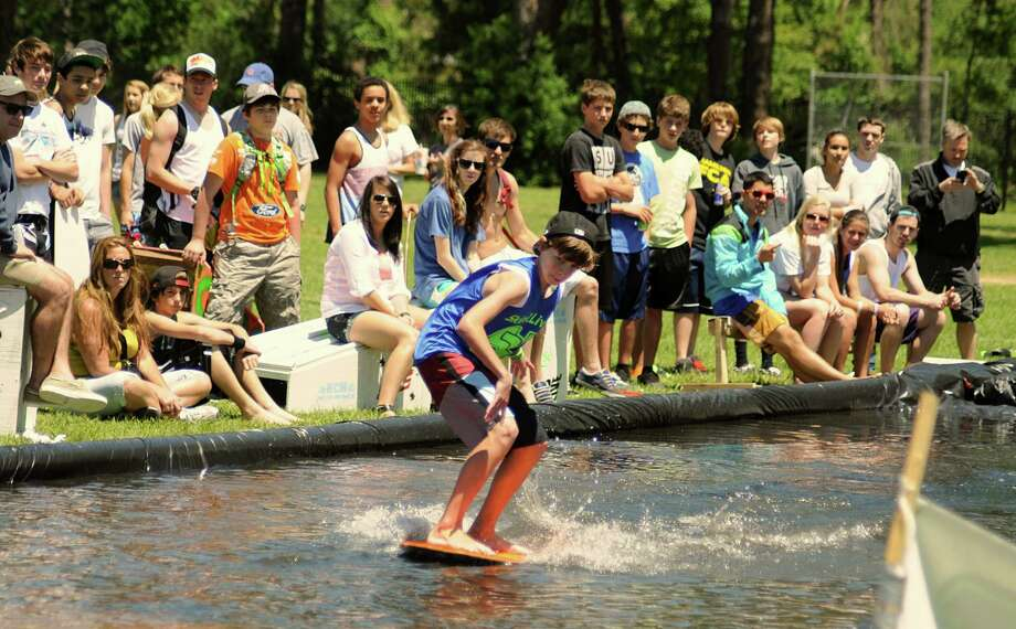 Spectators watch Ryan Cook of Cypress as he performs a trick Saturday during the Skim2Live's 5th Annual Cypress Skim Jam at Millsap Elementary in Cypress. The Skim Jam is the largest skimboarding competition in the state of Texas. Money raised from the benefit competition goes to The Rose, a non-profit breast cancer organizer. Photo: David Hopper, For The Chronicle / freelance
