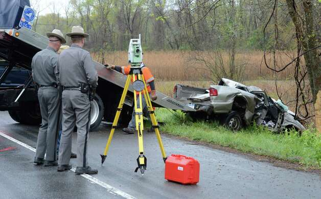 State Police accident reconstruction experts work on determining the cause of  a deadly crash early Monday morning  in Schodack. (Skip Dickstein / Times Union) Photo: SKIP DICKSTEIN / 2012