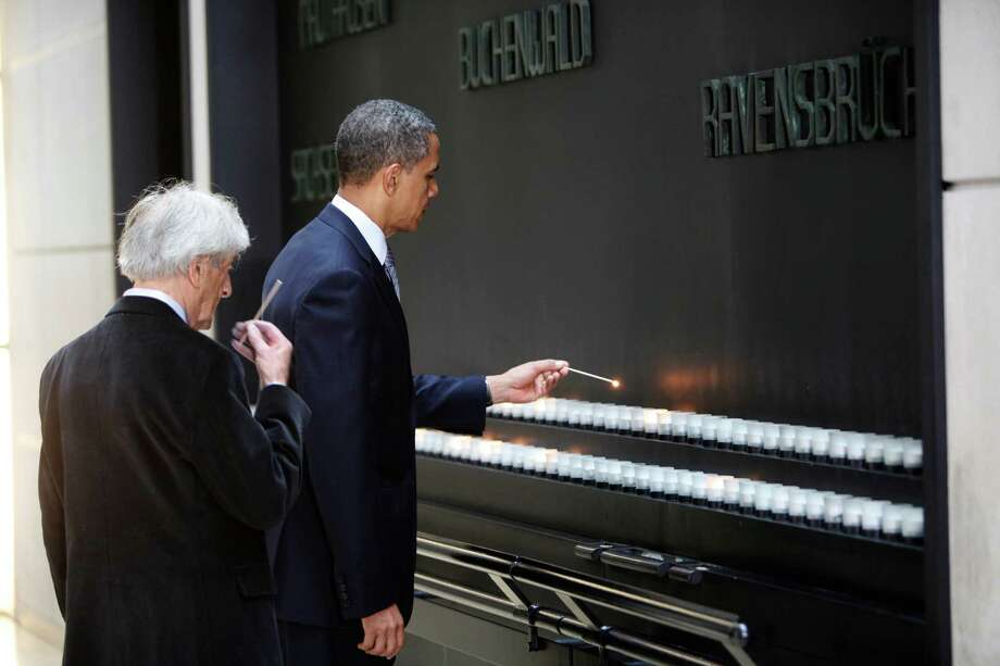 U.S. President Barack Obama (R) and Elie Wiesel light candles in the Hall of Remembrance at the Holocaust Museum April 23, 2012 in Washington, DC. Obama reportedly announced a new sanctions March 23, on Iran and Syria for entities and people using technology to target citizens. Photo: Pool, Getty Images / 2012 Getty Images