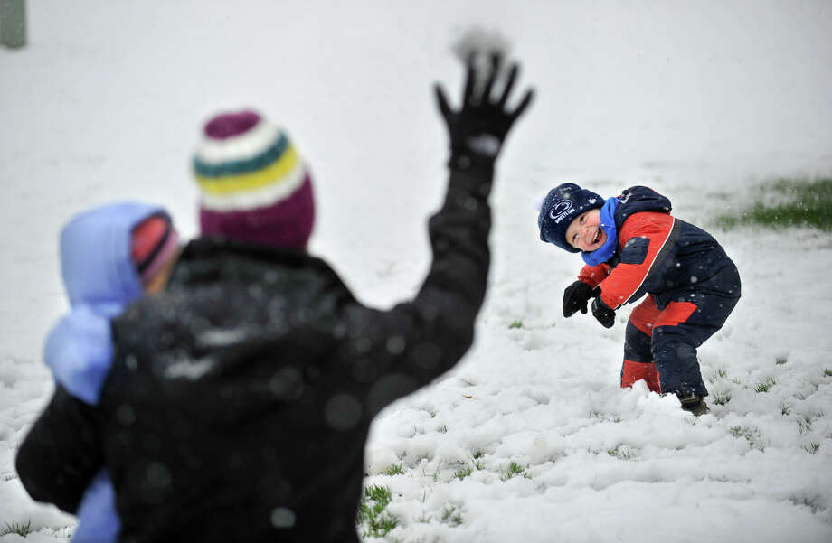 Evan Dreibelbis, 3, tries to avoid a snowball during a snowball fight  in fresh snow in their front yard with his mother Dana Dreibelbis and sister Elle Monday, April 23, 2012 in Pine Grove Mills, Pa. A spring nor'easter packing soaking rain and high winds churned up the Northeast Monday morning, unleashing a burst of winter and up to a foot of snow in higher elevations inland, closing some schools and sparking concerns of power outages(AP Photo/Centre Daily Times, Nabil K. Mark) Photo: Nabil K. Mark, Associated Press / Centre Daily Times