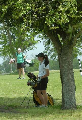 Felicia Sauceda, right, a Nederland golfer, waits to hit her ball down the fairway, while Little Cypress Mauriceville golfer Brooke Brasseaux, left, heads towards her own ball during play Thursday in the District 20-4A golf tournament at Bayou Din golf course.   Dave Ryan/The Enterprise Photo: Dave Ryan / Beaumont