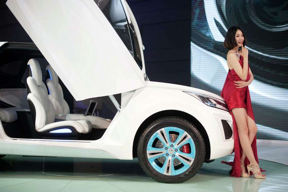 A model stands beside a 'Haval E' car by Chinese manufacturer Great Wall Motors, at the Auto China 2012 car show in Beijing on April 23, 2012. Beijing is hosting the Auto China 2012 exhiition in which top world carmakers will roll out a host of new models as they scramble for an edge amid sharply slowing sales in the planet's largest automobile market. The show runs until May 2.  TOPSHOTS          AFP PHOTO / Ed Jones Photo: ED JONES, AFP/Getty Images / AFP