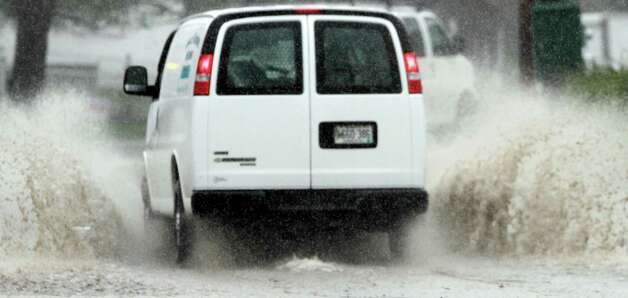 The driver of a vehicle navigates through a flooded portion of a street in Brunswick, Maine on Monday. The state is receiving its first major rain storm during the month of April. A spring nor'easter packing soaking rain and high winds churned up the Northeast Monday morning, unleashing a burst of winter and up to a foot of snow in higher elevations inland, closing some schools and sparking concerns of power outages. Photo: AP
