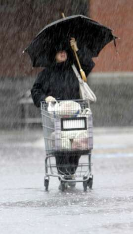 A shopper braves heavy rain while leaving a grocery store in Brunswick, Maine on Monday,. The state is receiving its first major rain storm during the month of April. A spring nor'easter packing soaking rain and high winds churned up the Northeast Monday morning, unleashing a burst of winter and up to a foot of snow in higher elevations inland, closing some schools and sparking concerns of power outages. Photo: AP