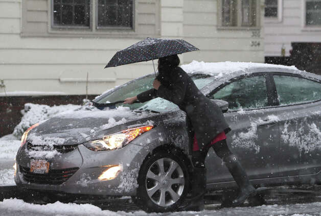 Renee Schechinger of Rochester brushes snow off her car on Oxford Street before heading off to work on Monday. A spring nor'easter dumped up to six inches of snow in sections of western New York and northwestern Pennsylvania Monday and was expected to keep piling it on through Tuesday in areas that were basking in 80-degree temperatures a month ago. (AP Photo/Democrat and Chronicle, Tina Yee)  Photo: AP
