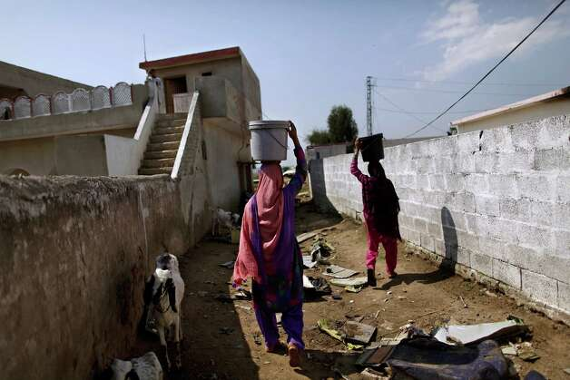 Pakistani women carrying water over their head, walk back to their homes on Monday through a path, with  parts of a Bhoja Air Boeing 737 passenger plane that crashed on Friday, killing all 127 people on board, remaining on the ground, on the outskirts of Islamabad, Pakistan. The Pakistani government mandated Sunday that all airplanes operated by private airlines must undergo a new inspection to determine whether they are safe to fly, days after a crash near the capital killed 127 people.The Bhoja Air crash Friday was the second in Pakistan in less than two years involving a private Pakistani airline. In both cases, the planes went down in bad weather as they approached the main airport in Islamabad. (AP Photo/Muhammed Muheisen) Photo: Muhammed Muheisen, ASSOCIATED PRESS / AP2012