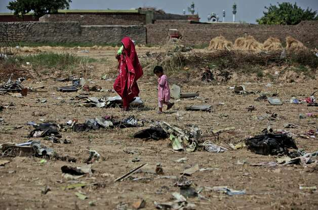 A Pakistani woman and a girl on Moonday walk by the wreckage of a Bhoja Air Boeing 737 passenger plane that crashed on Friday, killing all 127 people on board, on the outskirts of Islamabad, Pakistan. The Pakistani government mandated Sunday that all airplanes operated by private airlines must undergo a new inspection to determine whether they are safe to fly, days after a crash near the capital killed 127 people.The Bhoja Air crash Friday was the second in Pakistan in less than two years involving a private Pakistani airline. In both cases, the planes went down in bad weather as they approached the main airport in Islamabad. (AP Photo/Nathalie Bardou) Photo: Nathalie Bardou, ASSOCIATED PRESS / AP2012