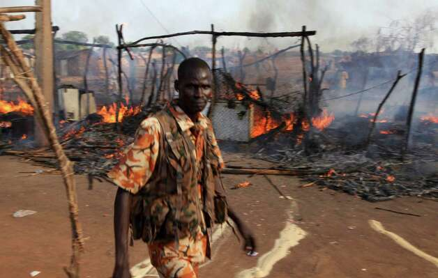 A policeman walks past the smouldering remains of a market in Rubkona near Bentiu in South Sudan Monday. A boy was killed and at least two people were wounded Monday when Sudanese aircraft bombed an area near the town of Bentiu in South Sudan, an official and witness said, increasing the threat of a full-scale war breaking out between the two nations. (AP Photo/Michael Onyiego) Photo: Michael Onyiego, ASSOCIATED PRESS / AP2012