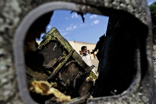 A Pakistani is seen Monday through the wreckage of a Bhoja Air Boeing 737 passenger plane that crashed on Friday, killing all 127 people on board, on the outskirts of Islamabad, Pakistan. The Pakistani government mandated Sunday that all airplanes operated by private airlines must undergo a new inspection to determine whether they are safe to fly, days after a crash near the capital killed 127 people.The Bhoja Air crash Friday was the second in Pakistan in less than two years involving a private Pakistani airline. In both cases, the planes went down in bad weather as they approached the main airport in Islamabad. (AP Photo/Muhammed Muheisen) Photo: Muhammed Muheisen, ASSOCIATED PRESS / AP2012
