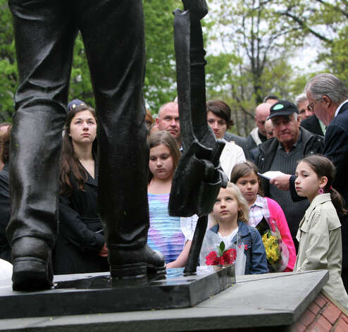 Francesca Perugini, 17, left, looks at the workers monument on Washington Ave. in Bridgeport, Conn. during a ceremony to honor the victims and the rescue workers on the 25th Anniversary of the L'Ambiance Plaza collapse on Monday, April 23, 2012. Perugini's grandfather, Angelantonio Perugini, was one of the 28 victims. Photo: B.K. Angeletti / Connecticut Post