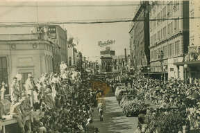 "Fiesta 1946 - Original caption: ""First entries in the historic Battle of Flowers parade -- a victory pageant which was declared by police officials to be the largest ever -- turn the corner at Broadway and Houston St. to begin the long trek over the two-mile parade loop in downtown San Antonio."""