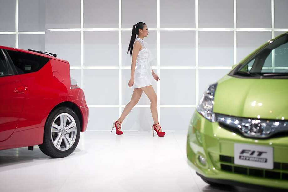 A model walks between Honda 'Fit' cars at the Auto China 2012 car show in Beijing on April 23, 2012. Beijing is hosting the Auto China 2012 exhiition in which top world carmakers will roll out a host of new models as they scramble for an edge amid sharply slowing sales in the planet's largest automobile market. The show runs until May 2.    AFP PHOTO/ TOPSHOTS/ ED JONES (Photo credit should read Ed Jones/AFP/Getty Images) Photo: Ed Jones, AFP/Getty Images