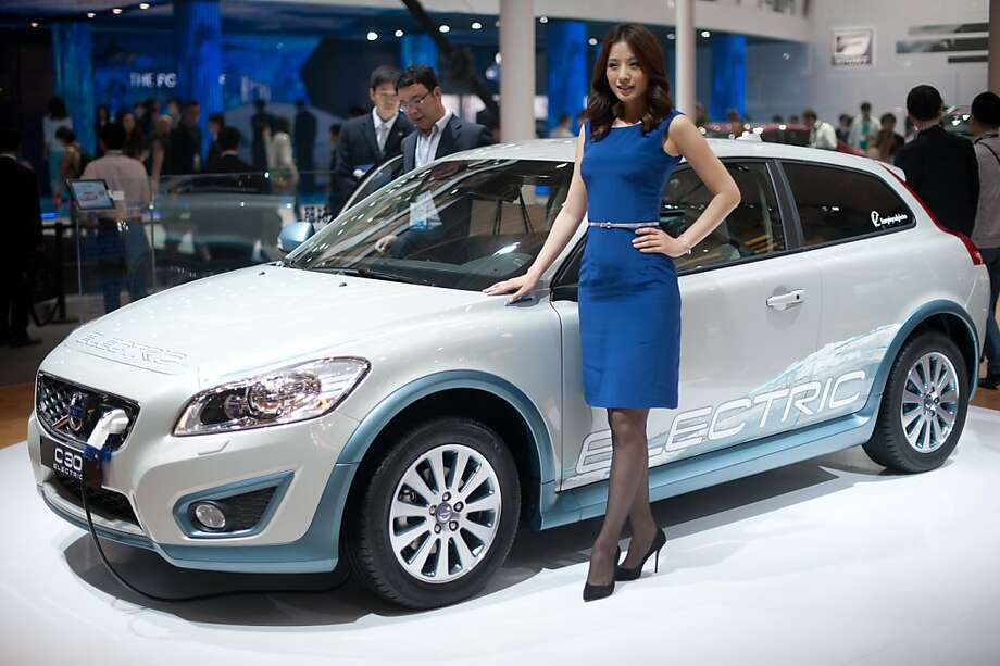 A model stands with a Volvo 'C-30' electric car at the Auto China 2012 car show in Beijing on April 23, 2012. Beijing is hosting the Auto China 2012 exhiition in which top world carmakers will roll out a host of new models as they scramble for an edge amid sharply slowing sales in the planet's largest automobile market. The show runs until May 2. AFP PHOTO / Ed Jones (Photo credit should read Ed Jones/AFP/Getty Images) Photo: Ed Jones, AFP/Getty Images