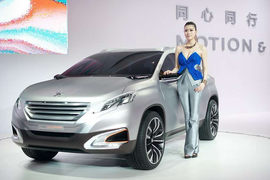 A model displays a Peugeot 'Urban Crossover' concept car at the Auto China 2012 car show in Beijing on April 23, 2012. Beijing is hosting the Auto China 2012 exhiition in which top world carmakers will roll out a host of new models as they scramble for an edge amid sharply slowing sales in the planet's largest automobile market. The show runs until May 2. AFP PHOTO / Ed Jones (Photo credit should read Ed Jones/AFP/Getty Images) Photo: Ed Jones, AFP/Getty Images