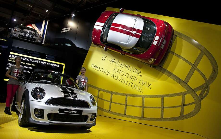 Models stand next to the Mini Cooper S on display at the Beijing International Automotive Exhibition in Beijing, China Monday, April 23, 2012. (AP Photo/Andy Wong) Photo: Andy Wong, Associated Press