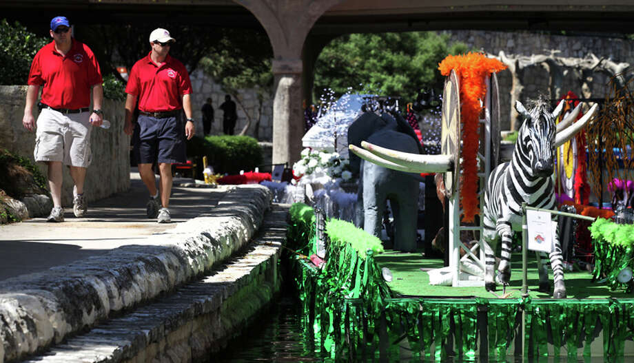 Members of the Texas Cavaliers, Rob Eversberg (left) and Brandon Clementson (right) check on the barges for tonight's Texas Cavalier's River Parade on the San Antonio River under Lexington Avenue on April 23, 2012. Photo: BOB OWEN, Bob Owen / San Antonio Express-News / © 2012 San Antonio Express-News