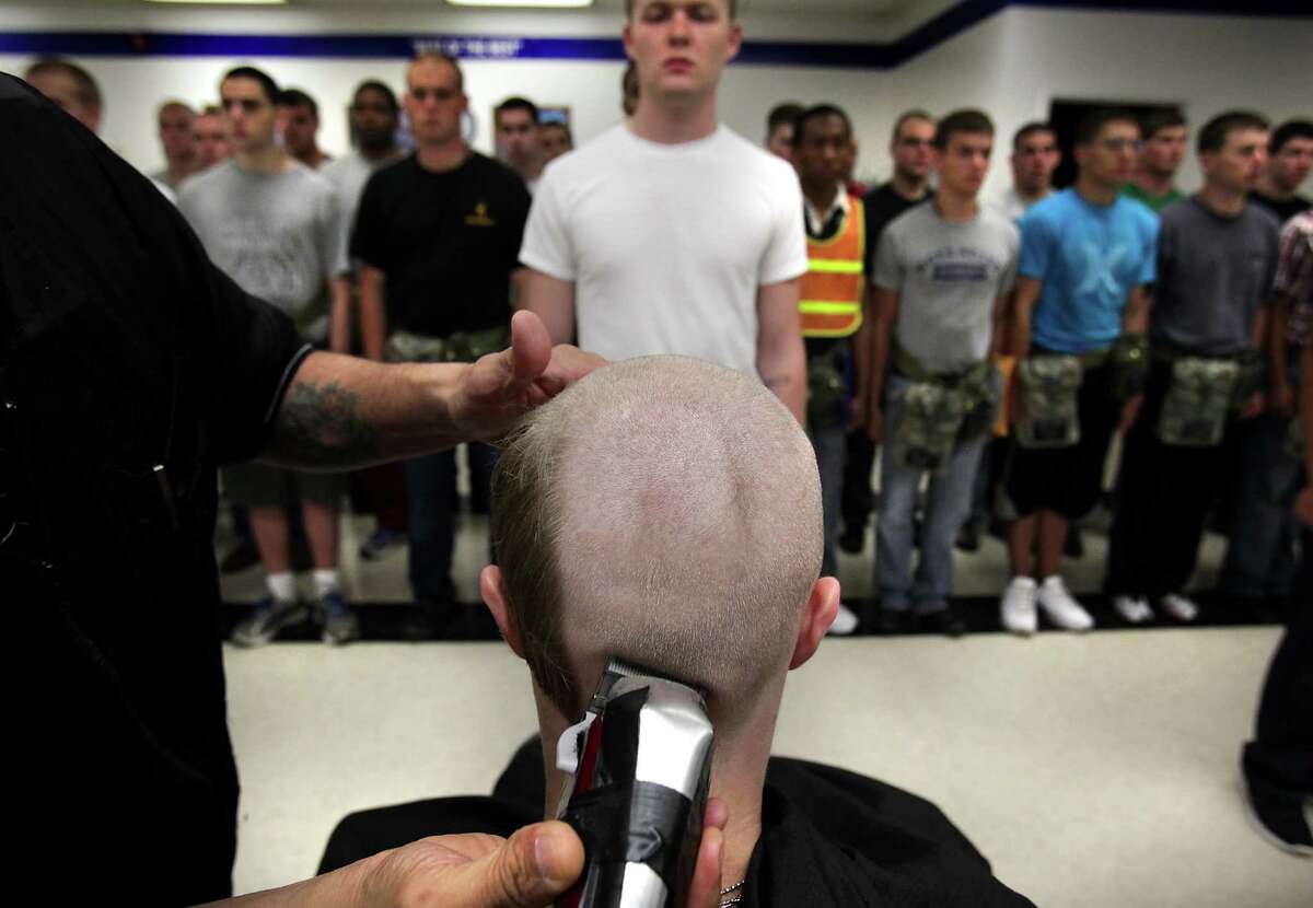 A new trainee gets his first military hair cut as others wait in line for the buzz cut. The first 72 hours of basic training at Lackland AFB is called Zero Week, when trainees learn to march and speak the Air Force way of life. Wednesday, April 18, 2012.