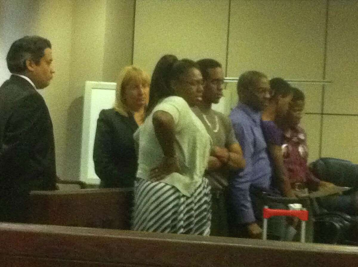 Prosecutors Dan Rodriguez and Jan Ischy stand to the side as murder victim Samuel Johnson Jr.'s fiancé, Erica Hinton (left) confronts Vanessa Cameron during a victim impact statement. Standing beside Hinton are Johnson's siblings and parents.
