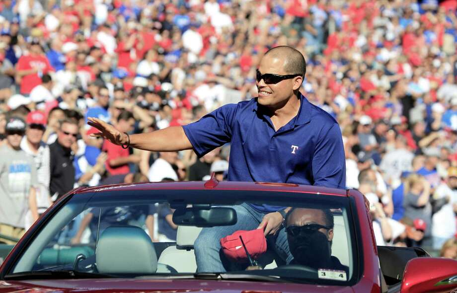 Former Texas Rangers catcher Ivan Rodriguez rides into the stadium and waves to fans before the baseball game between the New York Yankees and the Rangers on Monday, April 23, 2012, in Arlington, Texas. The Ranger honored Rodriguez, who recently announced his retirement. Photo: AP