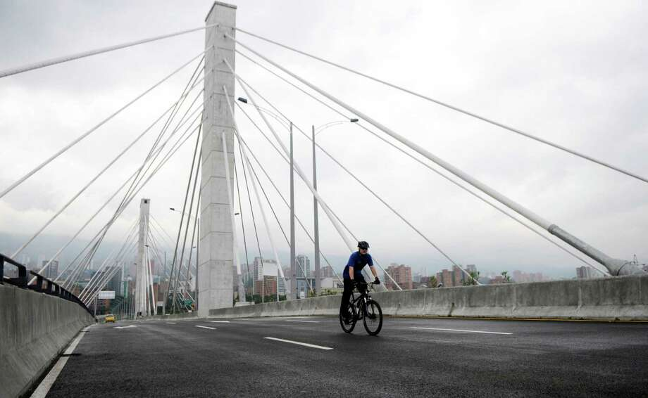 A lone bicyclist rides on a bridge, free of traffic, in Medellin, Colombia, Monday, April 23, 2012. Many residents of Medellin walked, biked, or took buses and taxis to their destinations honoring the car-free day. It was the fifth straight year for the Day Without Cars campaign in which cars are banned for a day to promote alternative transportation as a way to reduce smog. Photo: Luis Benavides, Associated Press / AP