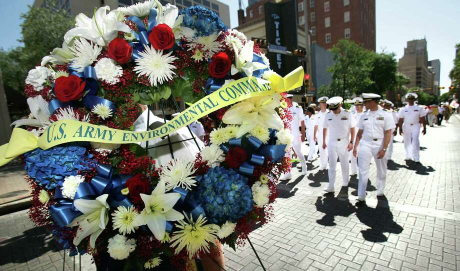 One of the many wreaths to be laid at The Alamo is carried in the silent procession along Houston St. during the 87th Annual Pilgrimage to The Alamo, Monday, April 23, 2012. Photo: BOB OWEN, San Antonio Express-News / © 2012 San Antonio Express-News