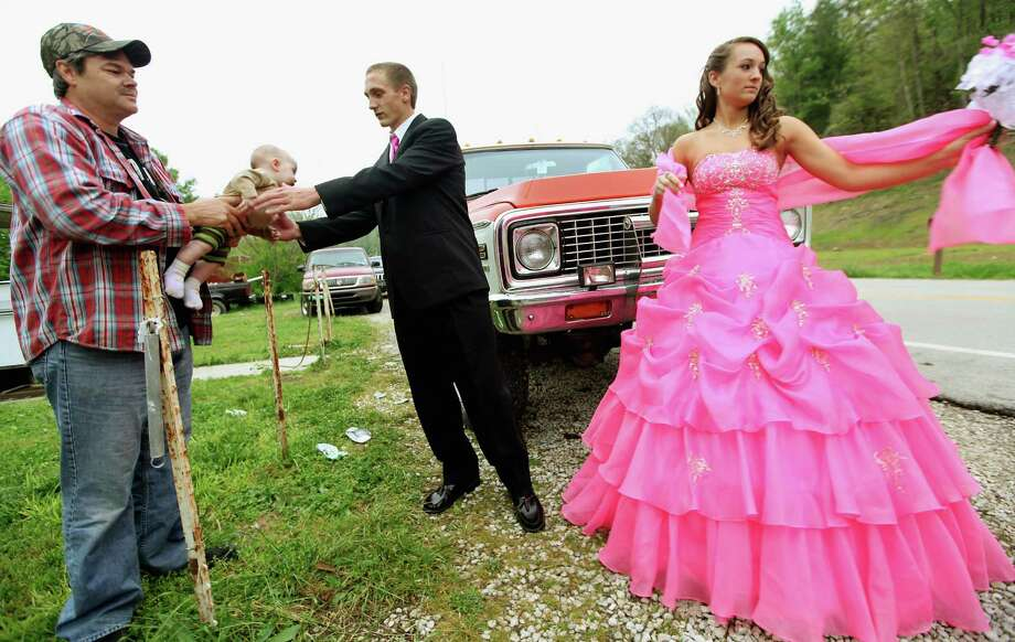 Dates Coty Shouse (C) and Destiny Duff (R) gather as Destiny's father Ronnie Duff (L) passes a baby to be photographed while preparing for the Owsley County High School prom on April 21, 2012 in Booneville, Kentucky. Photo: Mario Tama, Getty Images / 2012 Getty Images