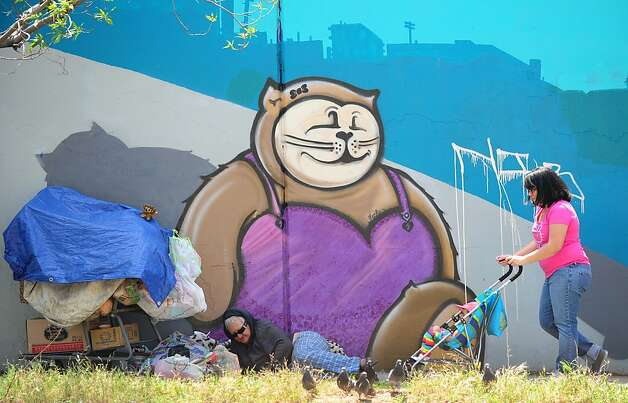 A homeless woman lays down beside her belongings in front of a wall of graffiti as a woman pushes a child in a stroller by on April 19, 2012 in Los Angeles, California.  New claims for US unemployment benefits inched lower last week, government data showed, in a report casting a cloud on the recovery in the labor market.  The new claims numbers, indicating the pace of layoffs, came amid signs of a sputtering recovery in the job market, where the unemployment rate fell to 8.2 percent in March from 8.3 percent in February but businesses put the brakes on hiring.    AFP PHOTO / Frederic J. BROWN (Photo credit should read FREDERIC J. BROWN/AFP/Getty Images) Photo: Frederic J. Brown, AFP/Getty Images