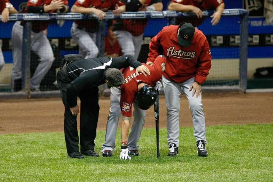 Jordan Schafer is attended to by a trainer and manager Brad Mills after he was hit by the baseball. (Scott Boehm / 2012 Getty Images)