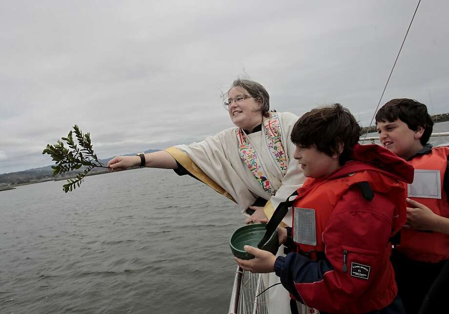 The Rev. Lisa Warner-Carey put a little english on her flinging of holy water.  Her sons Micah and Joshua looked on. For the first time since 1996, a traditional blessing of the fleet before salmon season was held at Pillar Point Harbor, near Half Moon Bay Monday April 23, 2012. The season opens for commercial fishermen May 1, but initial reports from sport boats say the salmon are running. Photo: Brant Ward, The Chronicle