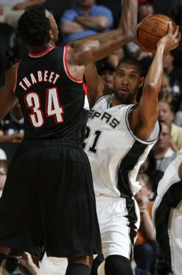 The Spurs' Tim Duncan looks to pass the ball as Portland Trail Blazers Hasheem Thabeet tries to block it during the first half at the AT&T Center, Monday, April 23, 2012. Jerry Lara/San Antonio Express-News (Jerry Lara / San Antonio Express-News)