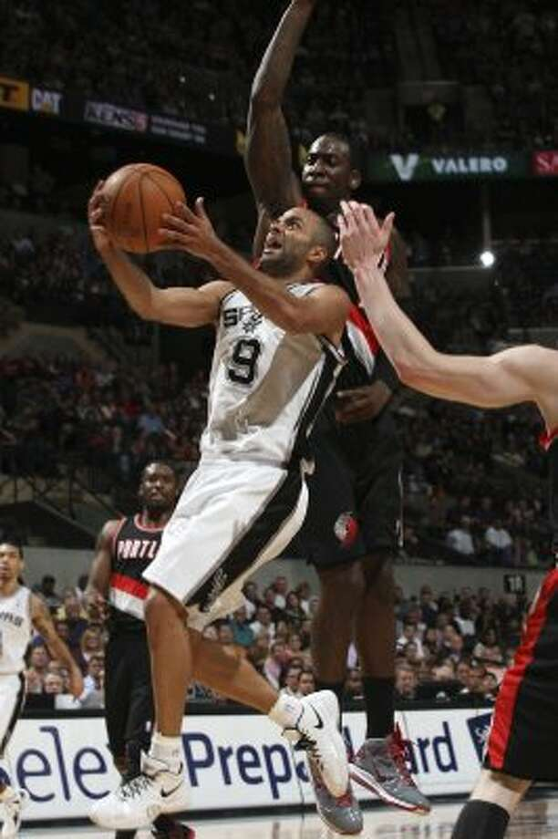 The Spurs'  Tony Parker drives to the basket past Portland Trail Blazers J.J. Hickson during the first half at the AT&T Center, Monday, April 23, 2012. Jerry Lara/San Antonio Express-News (Jerry Lara / San Antonio Express-News)