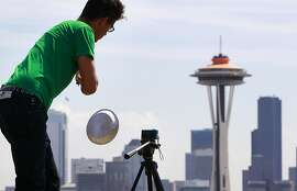 "Traeden Mathews dangles a pie tin in front of a tiny video camera and in view of the Space Needle as he films an extremely low-budget film about space invaders landing on Earth Monday, April 23, 2012, in Seattle. He was producing the tongue-in-cheek film for a friend's birthday. The top of the Space Needle behind sports a new coat of orange, called ""galaxy gold"" when it first appeared 50 years ago atop the structure, as part of the landmark's 50th anniversary celebration. The Space Needle, 605 feet tall, officially opened on the first day of the World's Fair April 21, 1962. (AP Photo/Elaine Thompson)"