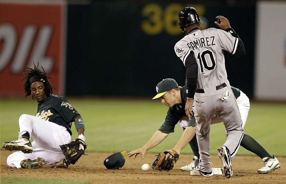 Oakland Athletics shortstop Cliff Pennington reaches for the ball as Chicago White Sox Alexei Ramirez (10) is safe at second base during the ninth inning of a baseball game Monday, April 23, 2012, in Oakland, Calif. At left is A's second baseman Jemile Weeks, who couldn't make the play on an RBI single hit by A.J. Pierzynski. (AP Photo/Ben Margot) Photo: Ben Margot, Associated Press