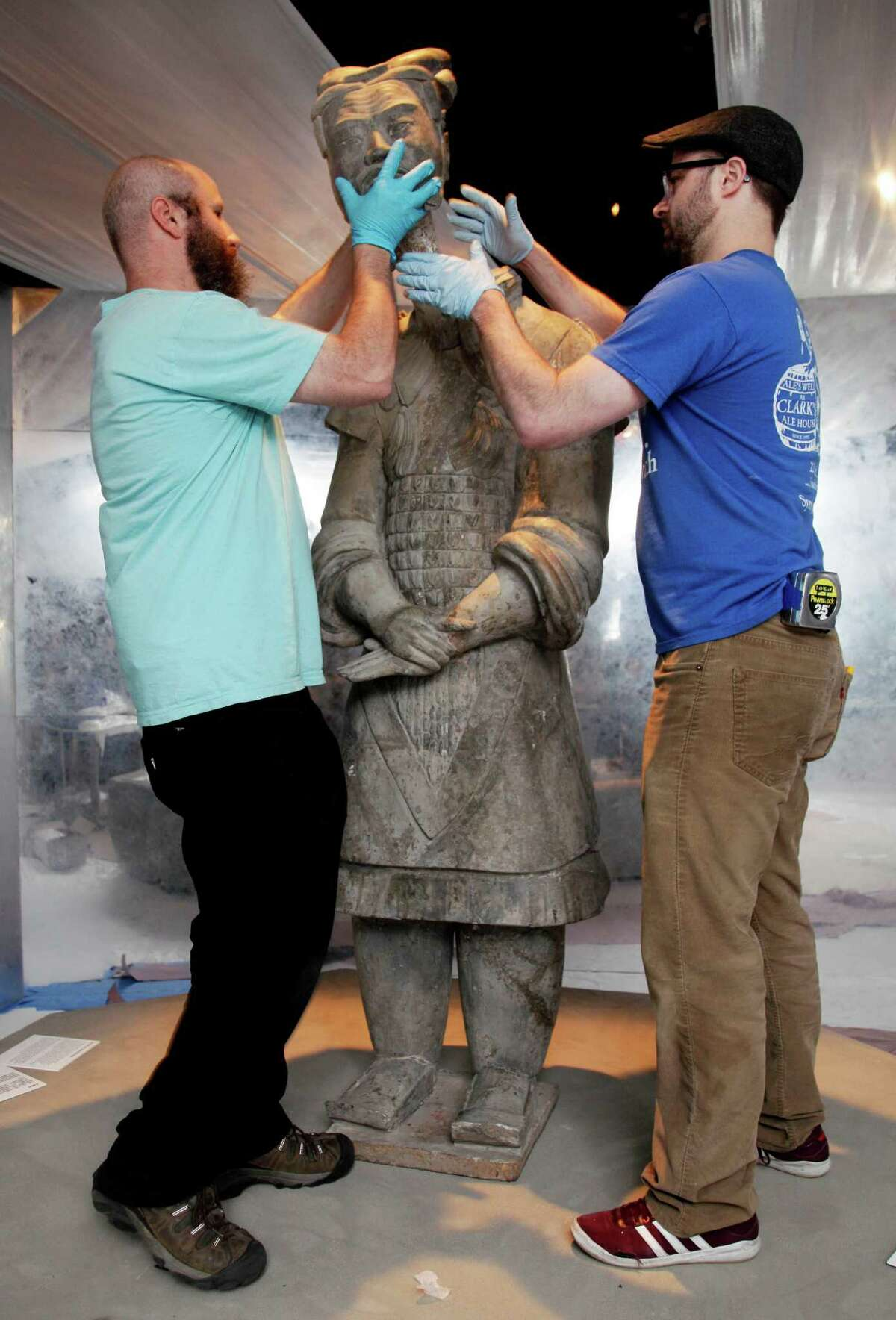 Art handlers place the head of a high-ranking officer, from the Qin Dynasty, 2211-206 BCE, Lintong, Shaanxi Province, as the they prepare the