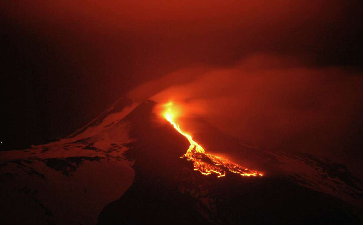 In this photo taken Monday, lava flows during an eruption of the snow capped Mount Etna volcano, near the Sicilian town of Catania, southern Italy. (AP Photo/Davide Caudullo, Lapresse)