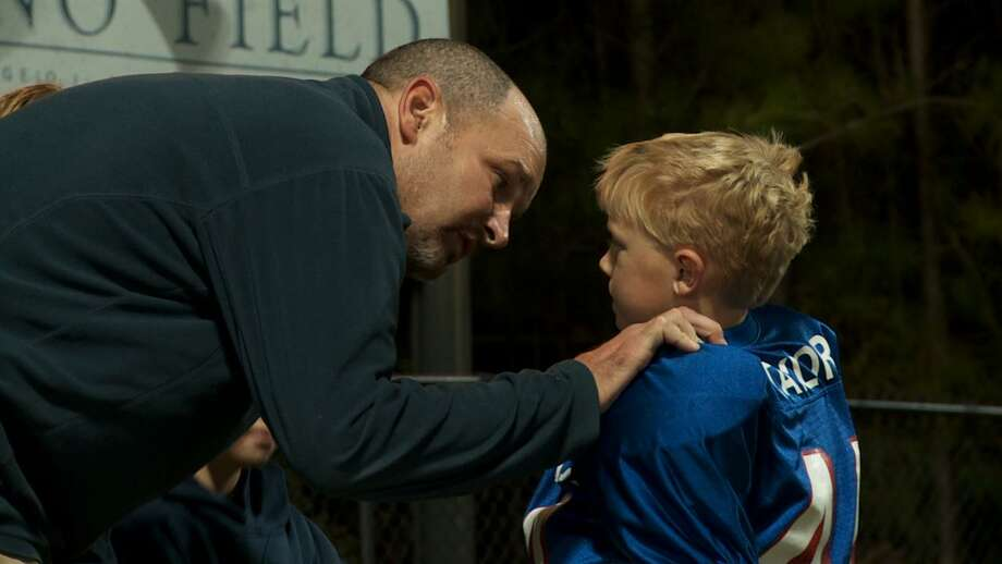 "Former pro football player Kevin Turner talks to a member of his son Cole's football team. Turner, who has ALS, is the subject of the documentary ""American Man."" Photo: Courtesy Jon Frankel"