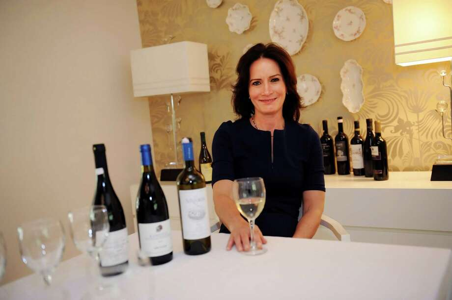 Nancy Mantzikos at her home in Riverside, Ct., displays wines from Greece Tuesday, April 23, 2012.  Mantzikos started Delfinia Group in Greenwich, tourism business focusing on Greece. She arranges wine tours for groups and offers individual travel planning. Photo: Helen Neafsey / Greenwich Time