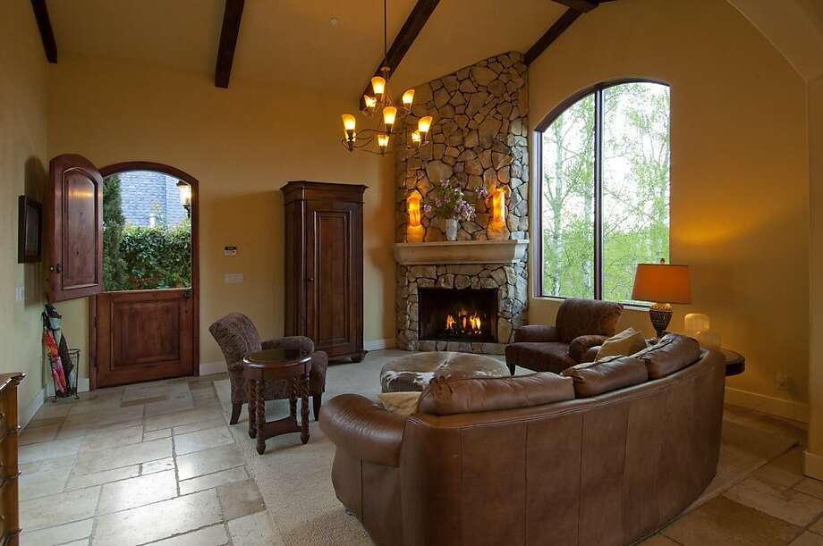 The living room has vaulted ceilings with exposed beams and a tall stone fireplace. Photo: Charles Simpson Photography