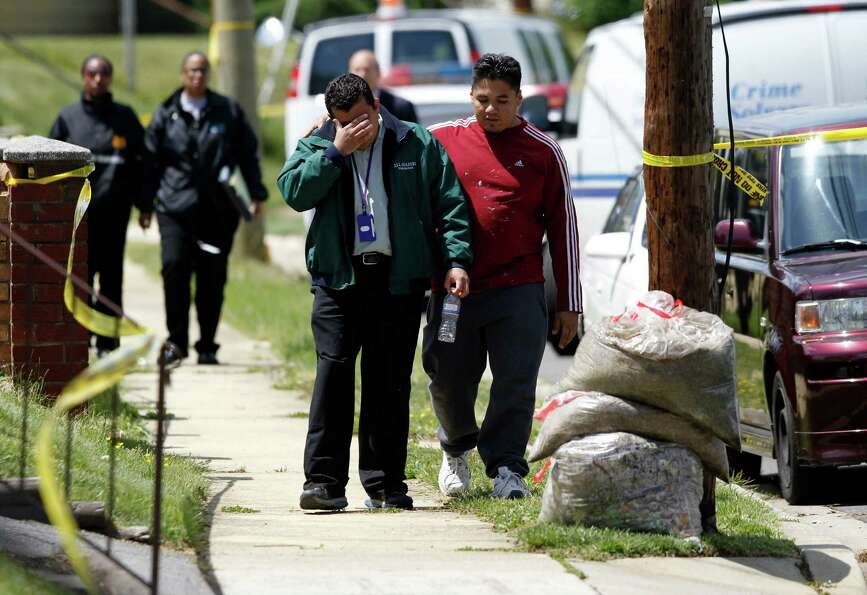 Marvin Chavez Quinteros, in green jacket, who discovered the bodies in his father's home, walks in O