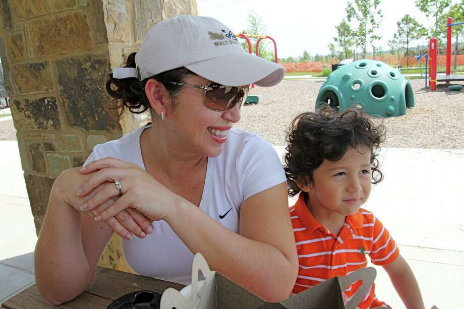 Maria Ramos enjoys a picnic at a pocket park with her son, Raphael, 2, at Cross Creek Ranch, 6450 Cross Creek Bend Lane in Fulshear. Photo: Suzanne Rehak