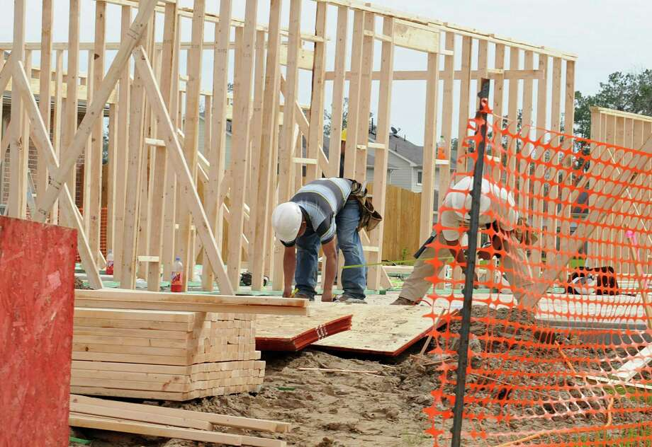 Construction workers gather lumber for framing the first floor of a new home in the King's Mill subdivision in Kingwood. Photo: David Hopper / freelance