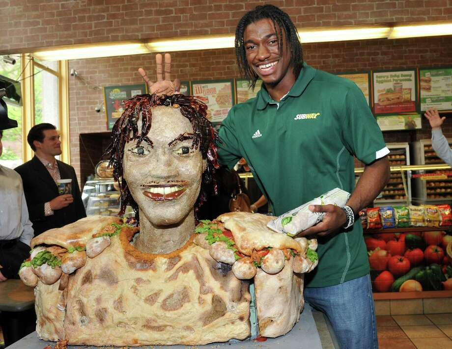 COMMERCIAL IMAGE - In this photograph taken by AP Images for SUBWAY, newest SUBWAY Famous Fan Robert Griffin III, top prospect in the 2012 NFL Draft, poses with his life-size statue made of SUBWAY Smokehouse BBQ Chicken, Tuesday, April 24, 2012, in New York.  The sculpture, made by artist James Victor of Conshohocken, Penn., is an artistic representation of the football star from the chest up and stands approximately three feet tall. Photo: AP IMAGES FOR SUBWAY